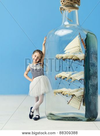 Little girl next to a ship in a bottle