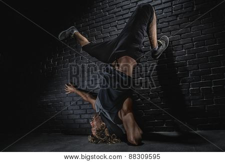 Young strong man modern dance on dark wall background