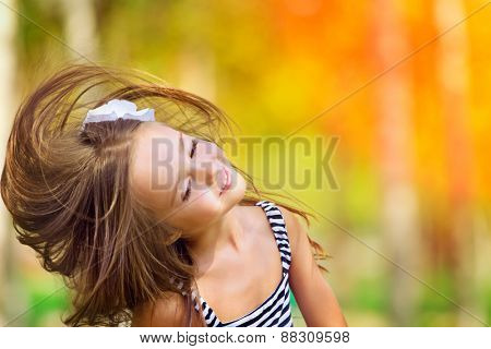 Portrait of Little caucasian girl  wind with flying hair, against green of summer park.