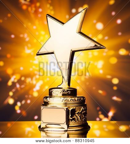 gold star trophy against shiny sparks background