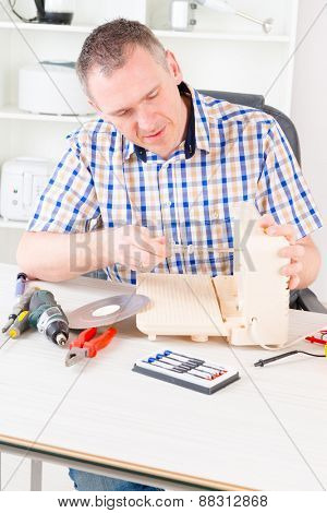 Man repairing a slicing machine at home appliance service workshop