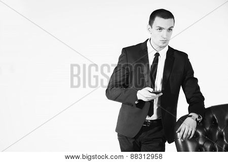 Male businessman sitting on black  leather chair on a white background.