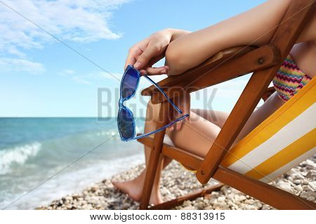 Hands With Sunglasses On The Beach