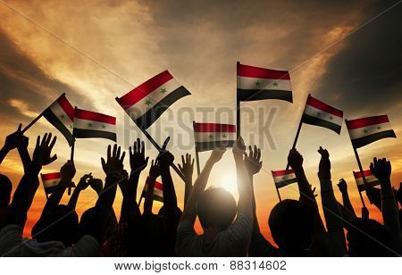 Group of People Waving Flag of Syria in Back Lit