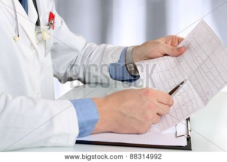 healthcare and medicine concept - doctor with clipboard analizing cardiogram