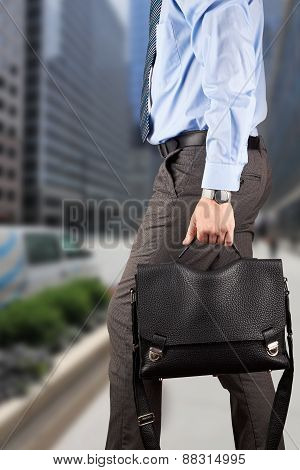 Businessman Walking And Holding  A  Leather Briefcase In His Hand