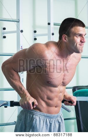 Muscular man working out with weights in gym.