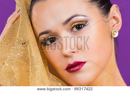 Girl with a professional makeup posing on a purple background.