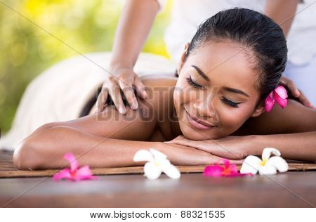 Young woman gets a massage with closed eyes
