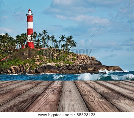 Wood planks floor with old lighthouse and sea waves in background