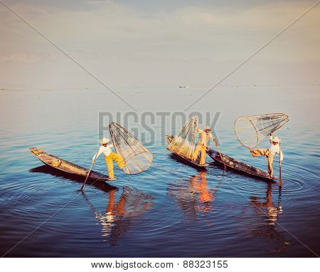 Traditional Burmese fishermen balancing with their fishing net on boats at Inle lake in Myanmar famous for their distinctive one legged rowing style. Vintage filtered retro effect hipster style image