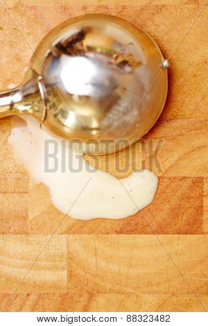 Ice cream disher with melted vanilla ice cream on a wooden board