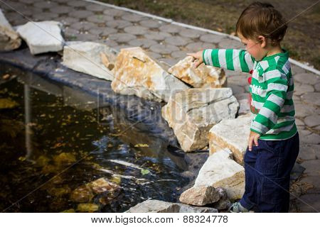 Little Boy Playing By The Fountain