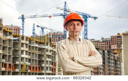 Workman In Red Helmet On Background Of Buildings