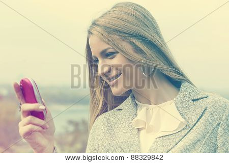 Young Woman With Pink Cell Phone Walking