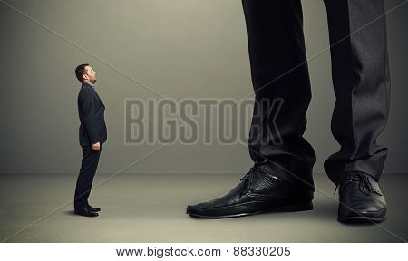 small amazed man looking up at big legs over grey background