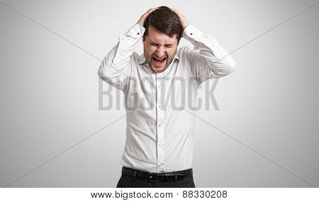 emotional man in white shirt holding his head and screaming in pain over light grey background