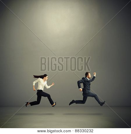 serious man and woman in formal wear running fast in grey empty room