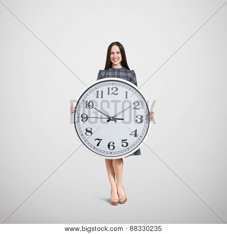 beautiful smiley woman holding big white clock and looking at camera over light grey background