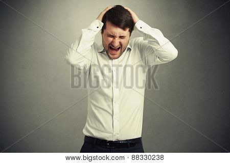 emotional creaming man in white shirt holding his head and closed his eyes strongly over grey background