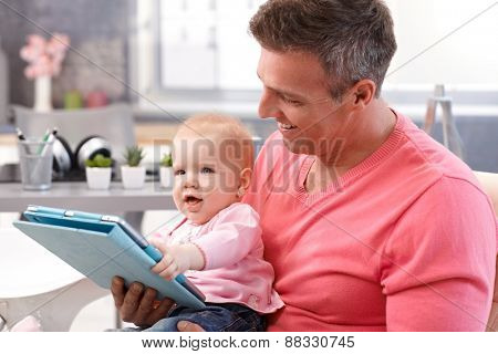 Baby girl playing with tablet, sitting on father's lap.