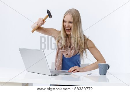Young woman sitting at desk, attacking laptop computer by hammer, shouting angry.