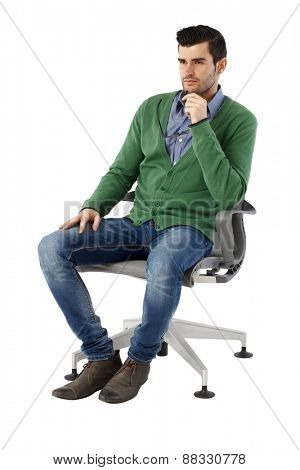 Handsome young businessman sitting and thinking in swivel chair over white background, looking away. Full size.