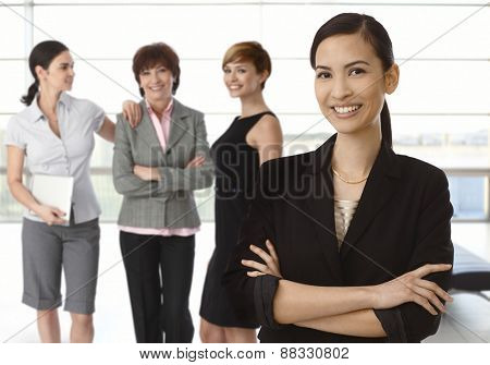 Team of diverse businesswomen, happy asian woman at front.