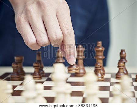 Hand of a man Moving A Pawn to Start a match
