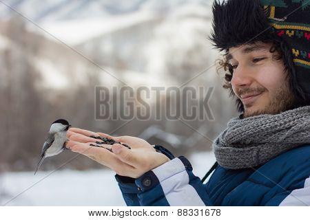 Man Feeding A Bird From The Hand