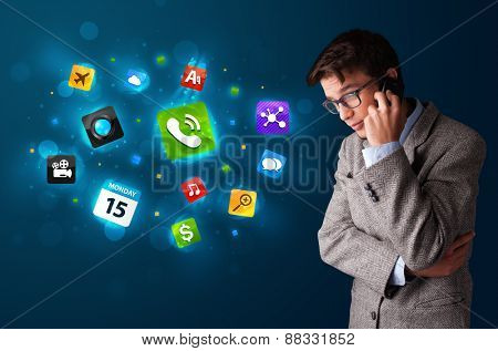 Handsome young man calling by phone with various icons