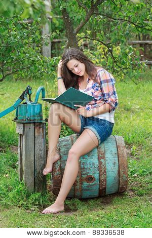 Reading barefoot brunette girl is sitting on rusty wooden barrel with