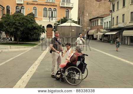 Venice, Mestre-june 29, 2014: Disabled Grandmother In A Wheelchair And Grandchild  On Piazza Erminio