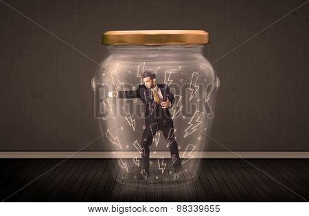 Businessman inside a glass jar with lightning drawings concept on background