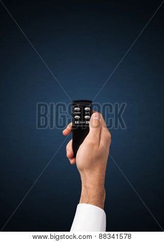 Hand holding a remote control on blue background