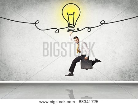 Businessman hanging on an idea bulb