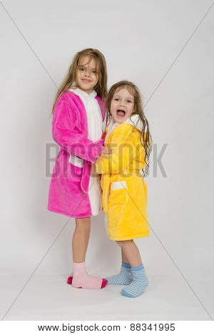 Two Girls In Gowns Hugging Each Other