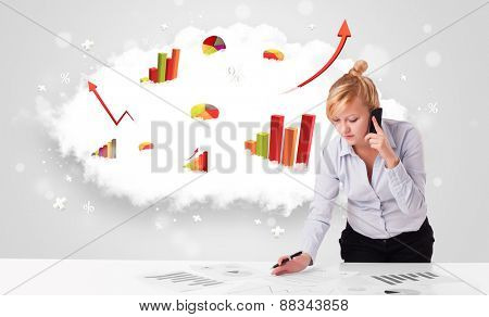 Beautiful young businesswoman with cloud in the background containing colorful graphs and diagrams