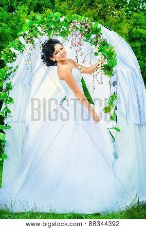 Beautiful elegant asian bride stands under the wedding arch. Wedding dress and accessories. Wedding decoration.