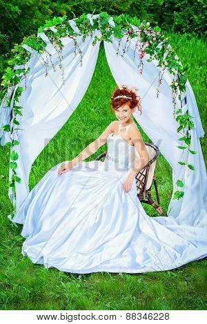 Beautiful bride with chaming red hair sitting under the wedding arch. Wedding dress and accessories. Wedding decoration.