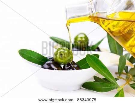 Olive Oil. Pouring Virgin Olive Oil on olives close up. Olives and Healthy Olive oil being poured from glass bottle. Isolated on white. Diet. Bottle of olive oil. Dieting concept. Healthy food