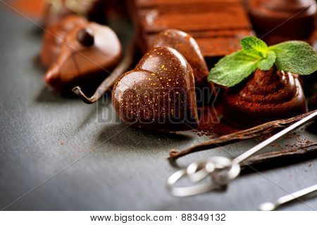 Chocolates. Chocolate sweets. Heart shaped praline. Assortment of fine chocolates in dark and milk chocolate with vanilla and mint. Praline