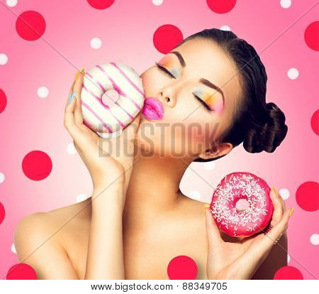 Beauty fashion model girl taking sweets and colorful donuts. Funny joyful Vogue styled woman choosing sweets on pink background. Diet, dieting concept. Junk food, Slimming, weight loss