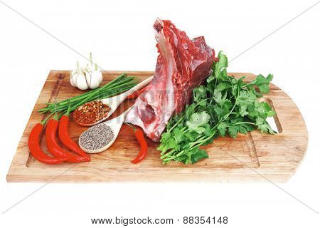 fresh meat : raw uncooked fat lamb pork rib with green stuff and red chili pepper on wooden plate isolated over white background