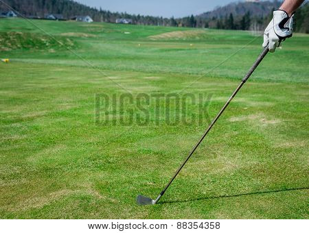 A Hand Is Holding A Golf Club And Measuring The Trajectory. Green Grass, White Glove With Shallow De