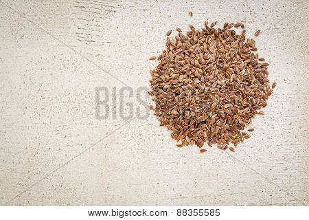 a small pile of brown flax seeds on a white painted, rustic barn wood with a copy space