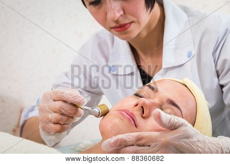 Beautician working on a face model in a spa salon. The process of cosmetic facial treatments.