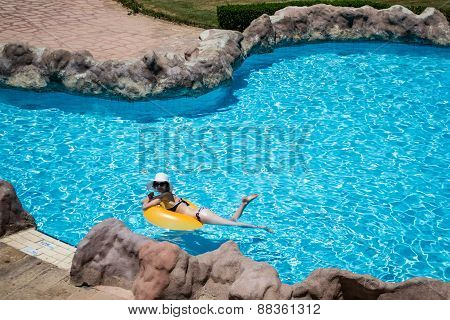 Beautiful Young Woman On Life Preserver In Pool
