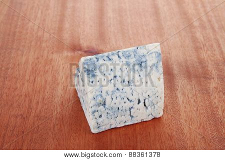 bit of aged french blue roquefort or cheese on wooden table