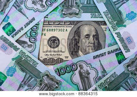 A hundred dollar bill on the background of Russian roubles